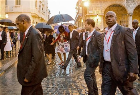 U.S. President Barack Obama, center, walks in the rain with first lady Michelle Obama, who is holding the arm of her mother Marian Robinson, during a walking tour of Old Havana, Cuba, Sunday, March 20, 2016. Obama became the first U.S. president to visit the island in nearly 90 years. (AP Photo/Pablo Martinez Monsivais)